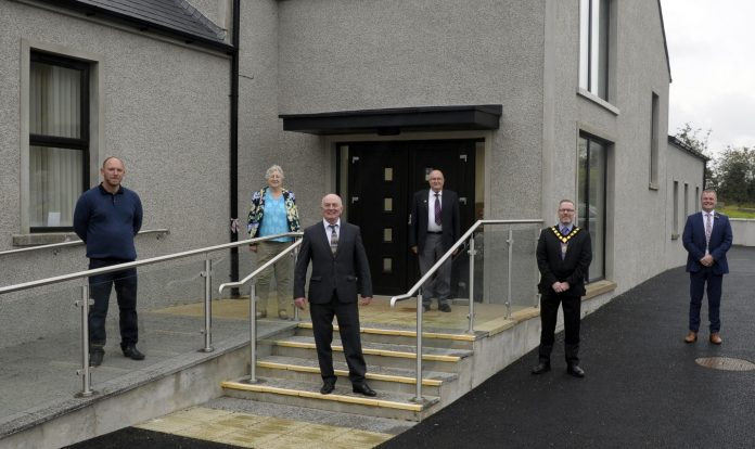 Five men and one woman pictured outside a newly renovated community hub.