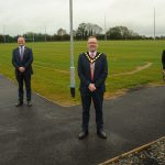 Four men and one woman pictured outside at a new football pitch and walking trail