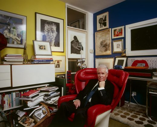 Alexander Walker sits surrounded by the many artworks he collected over many years