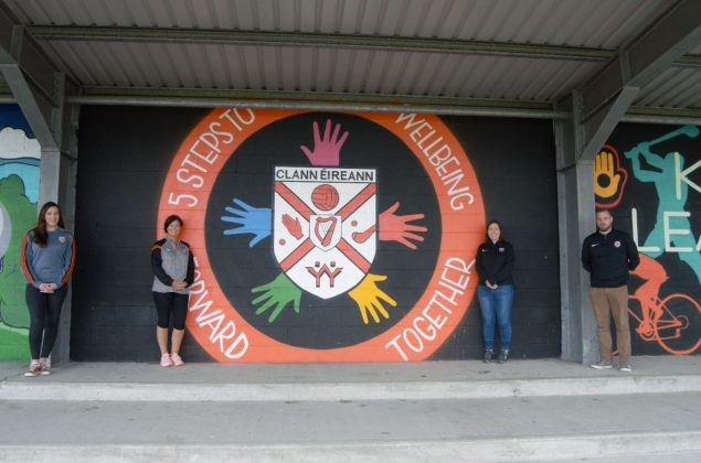 Four people standing beside a mural outside