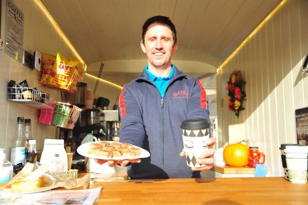 A man standing in a coffee kiosk holding a paper cup of coffee and a tray bake