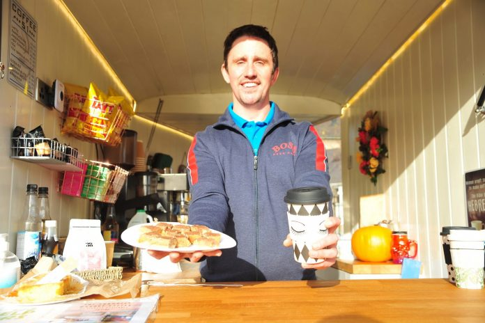 Man at a coffee kiosk holding a paper cup of tea and tray bake