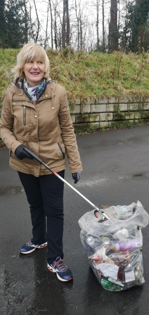 Picture of a women standing outside with a litter picker stick and bag of rubbish