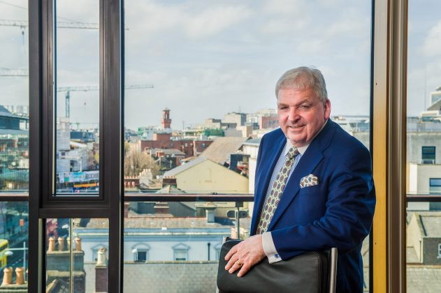 Business man in suit standing in an office in front of a window