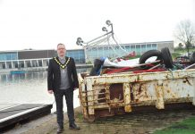 Man standing beside a skip filled with rubbish near a lake