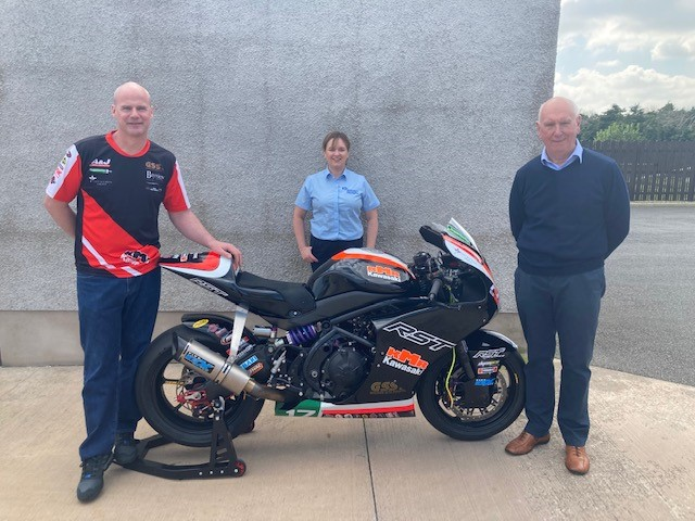The photo shows Ryan Farquhar, Gwen Bartley and Billy Stewart with a motorbike.
