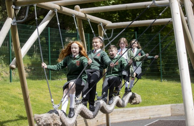 three school girls and two school boys play on new play park equipment