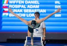 Male swimmer jumping off diving board