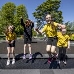 four school girls play on new play park equipment