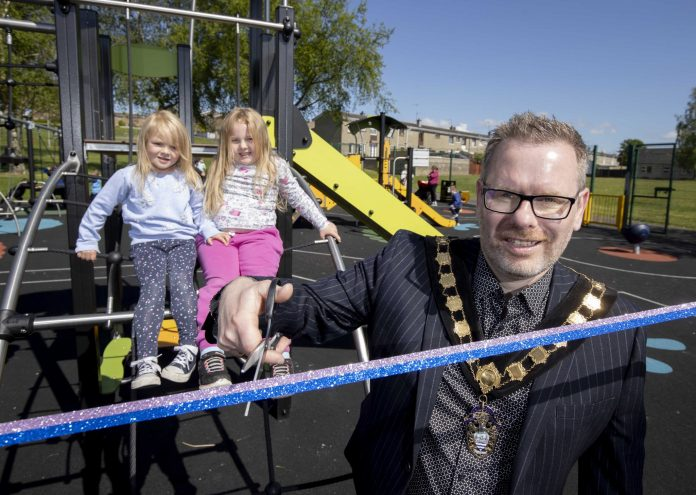 Male Lord Mayor cuts ribbon to new play park with two young girls in background