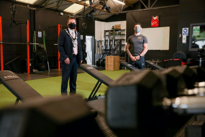 Two males standing indoors in gym