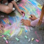 two teens using chalk on pavement